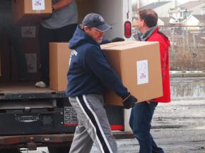 Pat Doherty, President of Oceanside American LL, carries a box to its new home